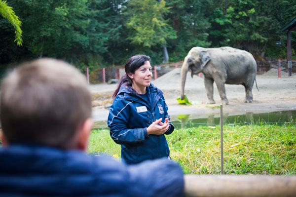 Woman talking to a crowd with an elephant in the background.